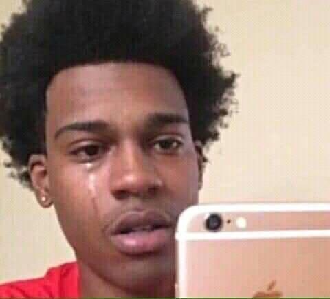 Anh da đen tóc xù vừa xem điện thoại vừa khóc